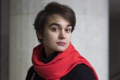年轻忧郁妇女剧烈的画象一条红色围巾的对cocrete墙壁 寂寞的概念 免版税库存照片