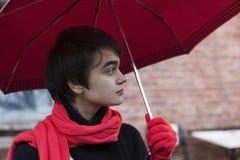 年轻忧郁妇女画象一条红色围巾的在多雨街道上的unmbrella下 寂寞的概念 复制空间 库存图片