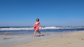 年轻快乐的妇女沿海滩走并且投掷她的磨损红色礼服和太阳镜的帽子 强的风雨如磐的波浪和蓝色sk 影视素材
