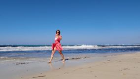 年轻快乐的妇女沿海滩走并且投掷她的磨损红色礼服和太阳镜的帽子 强的风雨如磐的波浪和蓝色sk 股票录像