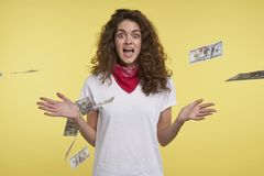 年轻快乐的妇女赢得全部现金,在飞钱和黄色背景 免版税库存图片