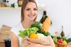 年轻快乐的微笑的妇女准备好烹调在厨房里 主妇拿着大纸袋有很多新鲜 免版税库存图片