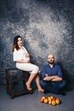 年轻怀孕的夫妇和苹果在地板上 概念甜家庭生活 免版税库存照片