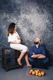 年轻怀孕的夫妇和苹果在地板上 概念甜家庭生活 库存照片