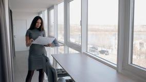 年轻性感的女实业家看图纸,站立在明亮的办公室 股票录像