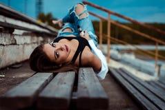 年轻性感的妇女在一个长木凳说谎 她在健身房的锻炼以后休假 室外 免版税库存照片