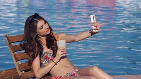 年轻性感的妇女在游泳池附近做selfie 股票视频