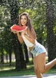 年轻性感的妇女画象水浪花的用西瓜 她有好柔和的皮肤,她的头发飞行,并且她微笑 库存照片