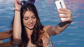 年轻性感的妇女的关闭在游泳池附近做selfie 影视素材