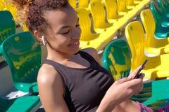 年轻性感的嬉戏黑人女孩单独坐观众的一把扶手椅子在体育场 在耳朵的白色Airpods 免版税图库摄影