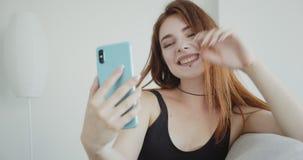 年轻性感的白种人女性特写镜头射击有黑色的紧身衣裤的在电话的一视频通话坐长沙发 股票视频