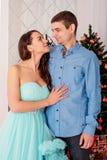 年轻恋人家庭凝视的目光夫妇在眼睛的与柔软在圣诞树附近的新年的前夕 免版税图库摄影