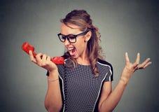 年轻恼怒的妇女叫喊入红色电话 免版税库存照片