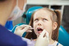 年轻患者坐在牙医椅子并且感觉痛苦 库存图片