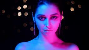 年轻惊人的白种人女性特写镜头射击有桃红色和蓝色霓虹灯和看照相机的bokeh背景的 股票视频
