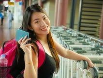 年轻愉快和可爱的亚裔中国妇女生活方式画象有背包微笑的激动和嬉戏对机场举行 免版税库存图片
