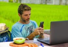 年轻愉快和可爱的人户外与便携式计算机和手机一起使用作为互联网旅行博客作者或数字式游牧人 免版税库存图片