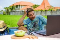 年轻愉快和可爱的人户外与便携式计算机和手机一起使用作为互联网旅行博客作者或数字式游牧人 库存图片