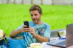 年轻愉快和可爱的人户外与便携式计算机和手机一起使用作为互联网旅行博客作者或数字式游牧人 免版税库存照片