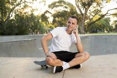 年轻愉快和可爱的美国人30s坐冰鞋板在体育搭乘训练以后谈话在手机 免版税库存照片