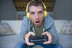 年轻愉快和激动的游戏玩家人生活方式画象有在家打电子游戏的耳机的获得在沙发长沙发holdi的乐趣 库存照片