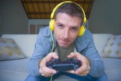 年轻愉快和激动的游戏玩家人生活方式画象有在家打电子游戏的耳机的获得在沙发长沙发holdi的乐趣 库存图片