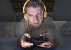 年轻愉快和激动的游戏玩家人生活方式画象有在家打电子游戏的耳机的获得在沙发长沙发holdi的乐趣 图库摄影