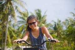年轻愉快和相当亚洲中国妇女骑马自行车在有棕榈树微笑的越南或泰国热带密林森林放松 库存照片