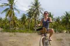 年轻愉快和相当亚洲中国妇女骑马自行车在有棕榈树微笑的越南或泰国热带密林森林放松 库存图片