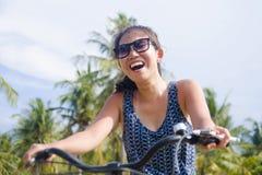 年轻愉快和相当亚洲中国妇女骑马自行车在有棕榈树微笑的越南或泰国热带密林森林放松 免版税库存图片