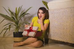 年轻愉快和美丽的亚裔印度尼西亚妇女打开的圣诞节或生日礼物箱子生活方式画象有红色丝带的 免版税库存照片