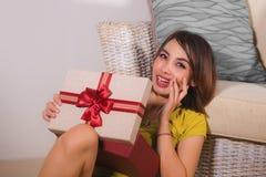 年轻愉快和美丽的亚裔印度尼西亚妇女打开的圣诞节或生日礼物箱子生活方式画象有红色丝带的 免版税库存图片