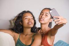 年轻愉快和美丽的亚裔姐妹或女朋友在家结合与手机长沙发的微笑的快乐的采取的selfie照片 免版税库存图片