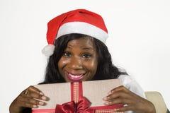 年轻愉快和美丽的黑人非裔美国人的妇女画象对当前箱子微笑负的圣诞老人项目帽子的快乐在Chri 库存照片
