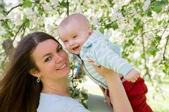 年轻愉快家庭走室外 照顾在手上的举行孩子并且高兴 他们一起是愉快的 微笑 库存图片