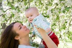 年轻愉快家庭走室外 照顾在手上的举行孩子并且高兴 他们一起是愉快的 微笑 图库摄影