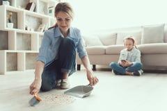 年轻愉快的与刷子的母亲详尽的地板 库存照片