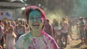 年轻愉快的亚裔女孩在夏天举在holi节日的手自白天,观看在照相机,颜色概念 股票录像