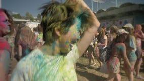 年轻愉快的亚裔女孩是跳舞和叫喊的与在holi节日的五颜六色的粉末自白天在夏天,颜色 股票录像