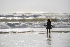 年轻愉快的亚裔妇女剪影放松看狂放的海在日落热带海滩挥动 免版税库存图片