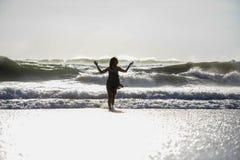 年轻愉快的亚裔妇女剪影放松看狂放的海在日落热带海滩挥动 免版税库存照片
