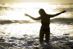 年轻愉快的亚裔妇女剪影放松看狂放的海在日落热带海滩挥动 库存照片