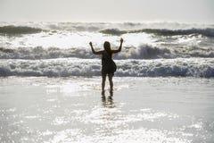 年轻愉快的亚裔妇女剪影放松看狂放的海在日落热带海滩挥动 免版税图库摄影