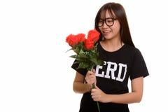 年轻愉快的亚裔微笑和拿着红色玫瑰的书呆子十几岁的女孩 图库摄影