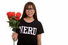 年轻愉快的亚裔微笑和拿着红色玫瑰的书呆子十几岁的女孩 免版税图库摄影