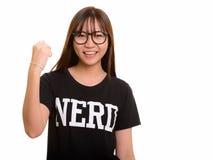 年轻愉快的亚裔看书呆子的十几岁的女孩微笑和刺激 免版税图库摄影