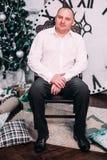 年轻愉快的人在接近圣诞树的椅子和礼物坐木背景 新年度和圣诞节庆祝 库存图片