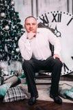 年轻愉快的人在接近圣诞树的椅子和礼物坐木背景 新年度和圣诞节庆祝 免版税库存照片