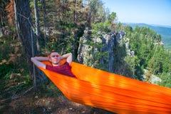 年轻愉快的人放松的在山顶部的吊床 夏天旅行生活方式 库存图片