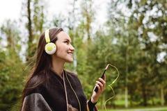 年轻愉快的从智能手机的妇女听的音乐有耳机的在一个安静的公园 免版税库存照片